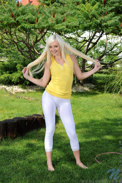 Platinum blonde teen peels off white leggings to pose nude on green grass